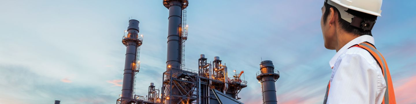 Engineer with notebook standing in front of oil refinery building structure in heavy petrochemical industry