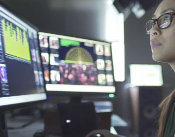 Close up stock image of a young asian woman sitting down at her desk where she's surrounded by 3 large computer monitors displaying out of focus images of people as thumbnails; crowds; graphs & scrolling text.