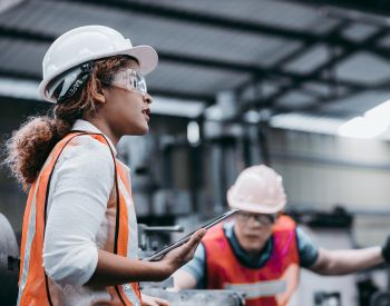 Female industrial engineer wearing a white helmet while standing in a heavy industrial factory behind she talking with workers, Various metal parts of the project